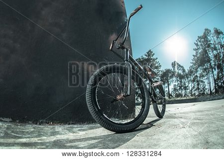 Bmx bike standing against black rough painted wall.