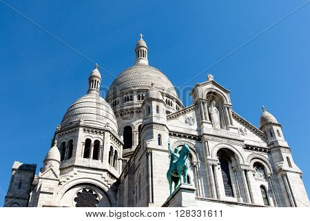 Color DSLR image of Basilica of the Sacre Couer on Montmartre, Paris, France with clear blue sky. Catholic church cathedral is popular Europe tourist destination. Horizontal with copy space for text.