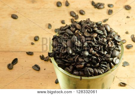 Whole Roasted Coffee Beans In Bowl And Glass And Wood Table