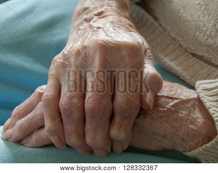 Close-up of woman gripping hand having arthritis
