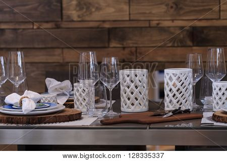 Rustic place setting with white candleholders and wine glasses on a country patio in summer.