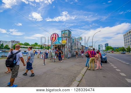 BERLIN, GERMANY - JUNE 06, 2015: Unidentified people visiting historic Berlin wall, actually full of graffitis, little shop on the side,