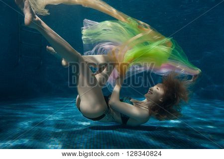 Woman lies on the bottom of the pool and playing with colorful fabrics.