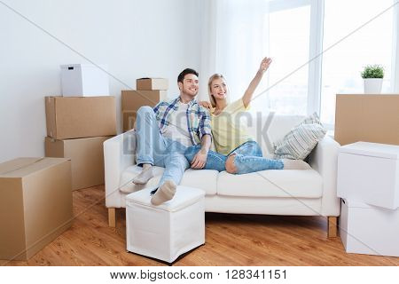 people, repair and real estate concept - smiling couple with boxes moving to new home and dreaming