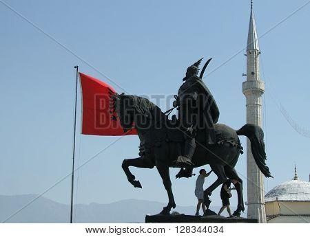 Skanderbeg's monument Tirana Albania Albanian national flag flying Ethem Bey Mosque minaret in the background