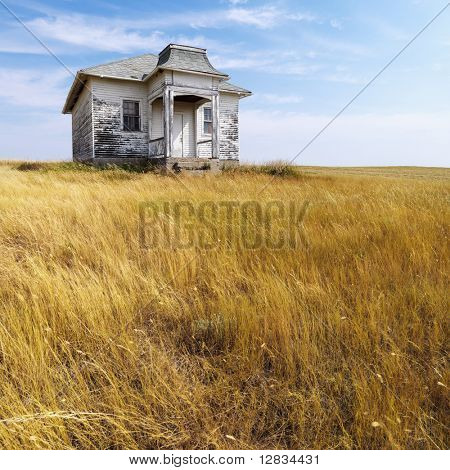 Weathered abandoned building in remote grassland.