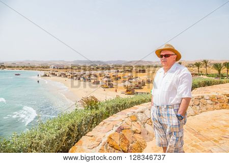 MARSA ALAM, EGYPT, MARCH 27, 2016: Senior tourist enjoys a beautiful sea view on Three Corners Equinox Beach Hotel terrace in Marsa Alam, Egypt
