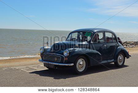 Felixstowe, Suffolk, England - May 01, 2016: Classic Blue Morris Minor 1000 being driven along Felixstowe seafront promenade.