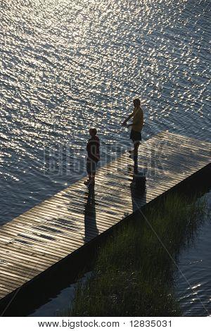 Birds eye view of two teenage boys fishing from dock at Bald Head Island, North Carolina.
