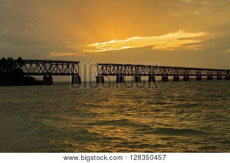 Beautiful colorful sunset or sunrise with broken bridge and sun rays spreading through purple clouds. Taken at Bahia Honda state park in the Florida Keys.