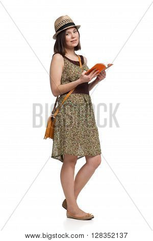 young pretty girl in summer dress and hat holding guidebook over white backgroud