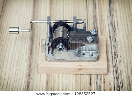 Old little music box on the wooden background. Retro style. Gift item. Old toy.
