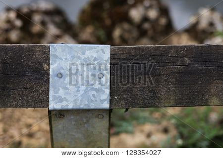 Galvanised steel sheet cover for old wood fence post joint around the pond