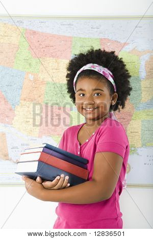 African American girl standing in front of USA map holding stack of books smiling at viewer.