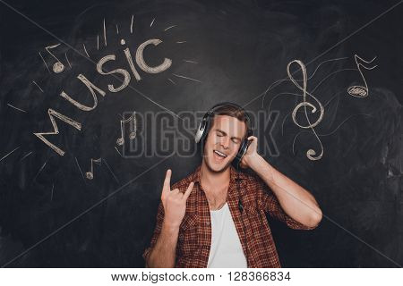 Portrait Of Man In Headphones Listening Music And Showing Rock Gesture
