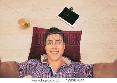 Cheerful Man Lying On The Floor On Pillow  And Making Selfie