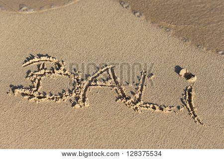 Inscription Bali On Sandy Beach With Wave's Foam