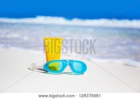 Sun Screen Lotion And Swimming Glasses On Beach
