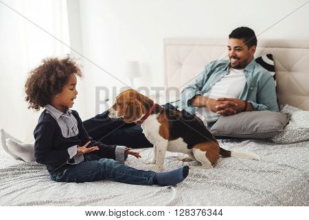Cute little girl playing with her dog in the bed.
