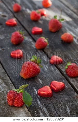 Strawberries And Candy On Wooden Table