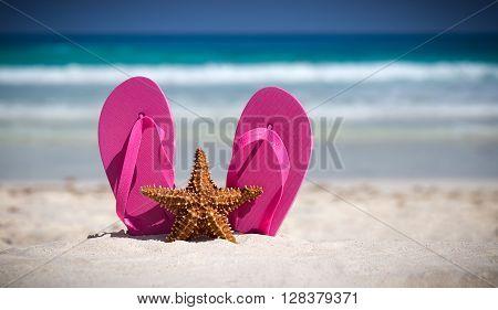 Pink Flip Flops And Starfish On White Sandy Beach