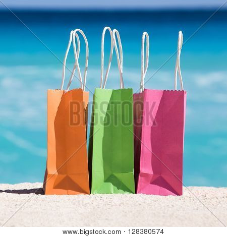 Shopping Bags On Sand Against Turquoise Caribbean Sea Water