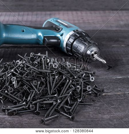 Pile Of Black Screws And Screwdriver  On Wooden Table