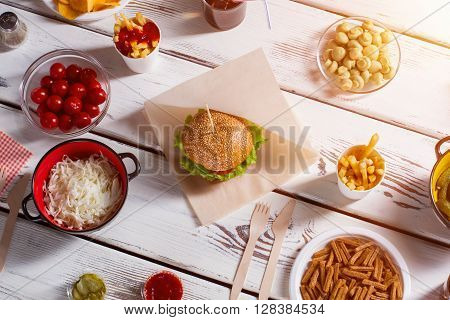 Burger, tomatoes and champignons. Mushroom bowl, burger and pepperbox. Picnic food on white table. Delicious weekend lunch. poster