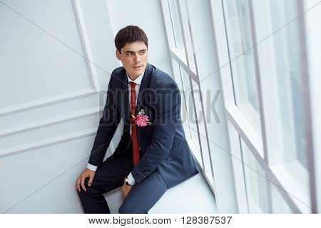 Gorgeous smiling groom. Handsome man in a suite with a buttonhole sitting on window sill and lookin in window indoors