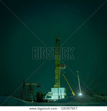 Night view of a derrick drilling and oil pump jack.