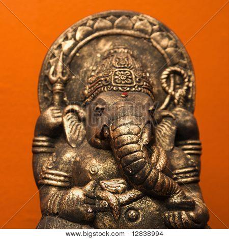 Statue of Hindu elephant Ganesha against orange wall.