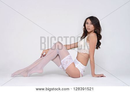 Beautiful sexy lady in elegant panties and stockings isolated on a white background. Fashion portrait of model indoors. Beauty woman with attractive body in lace lingerie. Female ass of naked girl