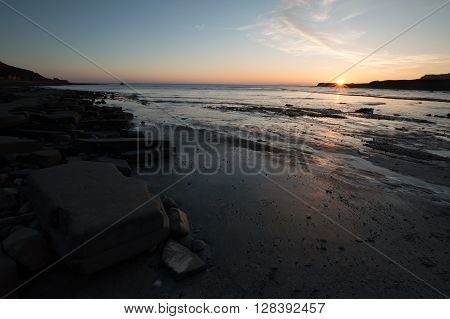 Sunset at Kimmeridge Bay, Dorset, with rocks in the foreground