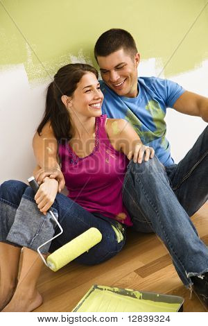 Couple sitting on floor smiling taking a break from painting home.