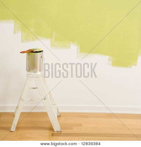 Paintbrush on can on top of step ladder with painted wall.