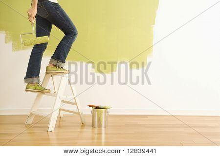 Legs of woman climbing stepladder holding paint roller.