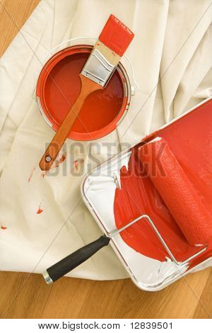 High angle view of painting supplies on drop cloth on wood floor.