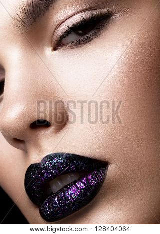 Portrait of a beautiful girl. Brilliant glossy lips closeup. Purple glitter on black lipstick.