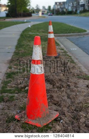 A dirty cone on a side walk at the end of the day
