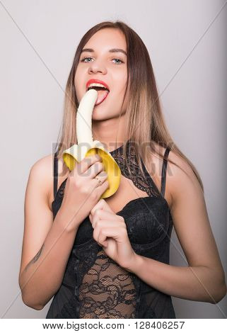 Young amazed woman in lacy lingerie holding a banana, she is going to eat a banana.