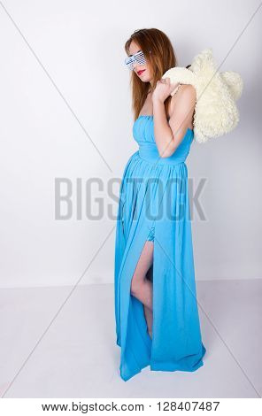 young redhead woman in a blue dress and disco glasses, hugging a teddy bear