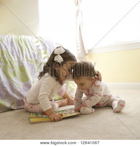 Caucasian girl children sitting on bedroom floor looking at book.