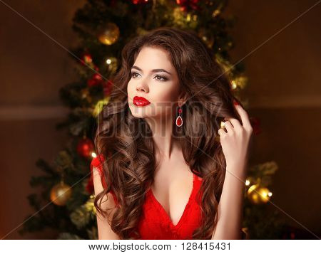 Christmas Woman. Long Hair. Fashion Earrings. Makeup. Beautiful Girl Portrait. Elegant Lady In Red D