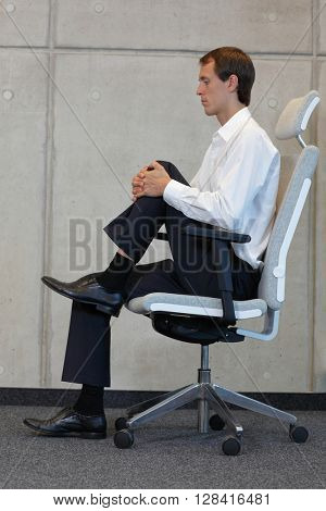 stretching on chair in office - business man exercising