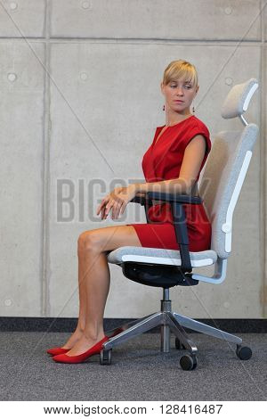stretching on chair in office - business woman exercising