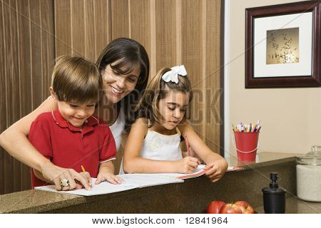 Hispanic mother helping children with homework.