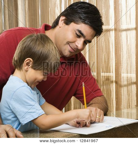 Hispanic father helping son with homework.