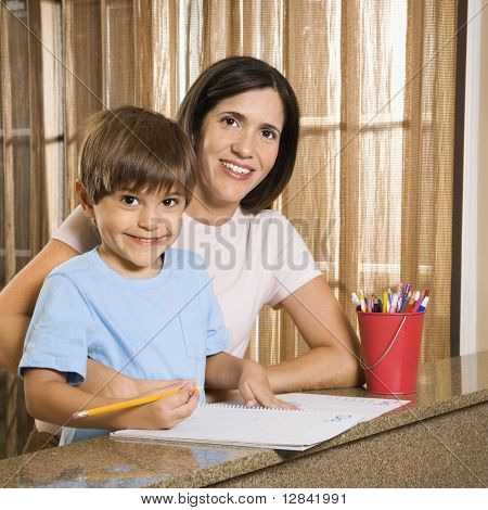 Hispanic mother and son with homework smiling at viewer.