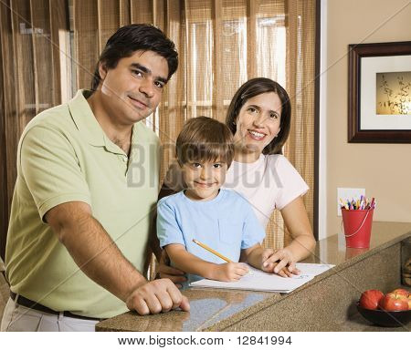 Hispanic parents and son with homework smiling at viewer.