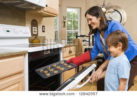 Side view of Hispanic mother and son putting cookies into oven.